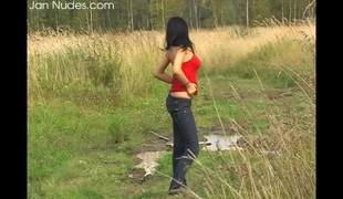 Dark-haired chick reveals her appealing body in the grassland